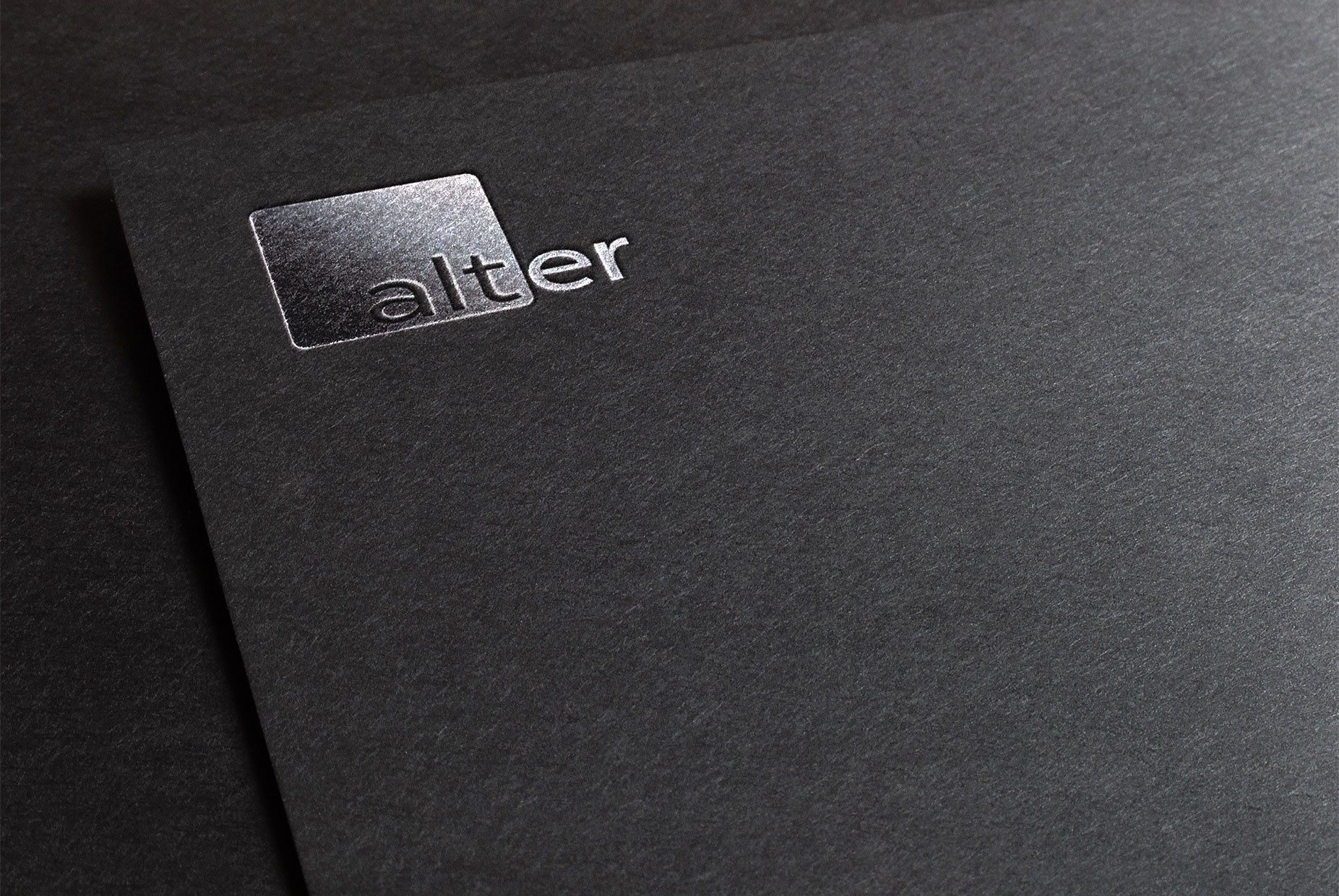 The Alter logo embossed in silver on black paper.