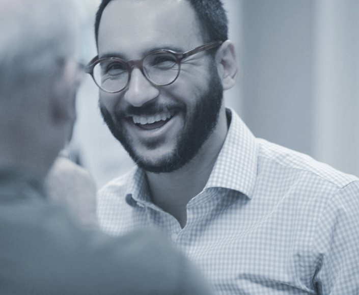 Portrait of George smiling and talking to a client.