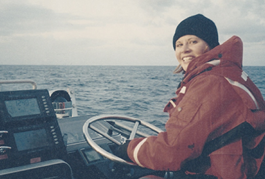 Heather Doucette driving a boat on the lake.