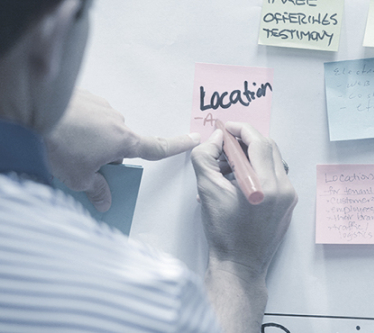 Man writing on a post-it note.